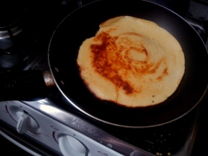 A parte de cima já está boa e a panqueca foi virada, para fritar a parte que agora está embaixo.