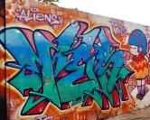 Primeira metade de muro com grafites de Testa, Karol, Ramar, Coral e Sro, no bairro Serra. Foto tirada por CMC em 9.5.2014.