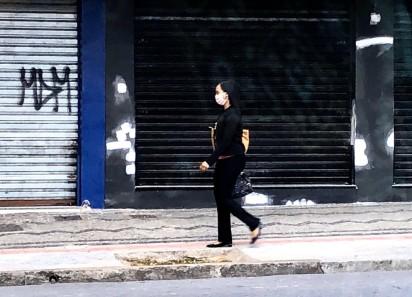 Pessoas usam máscaras nas ruas de BH. Na foto, pedestre na avenida Bias Fortes.