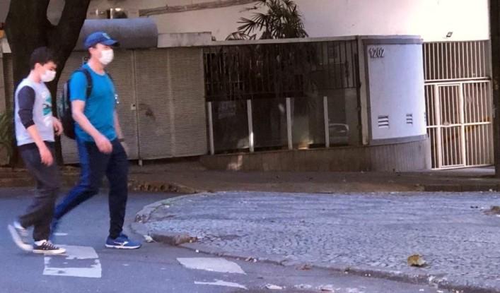 Pessoas usam máscaras nas ruas de BH. Na foto, pedestres na avenida Cristóvão Colombo